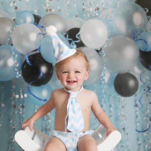 first birthday cakesmash baby boy smiling in party hat with blue balloon backdrop