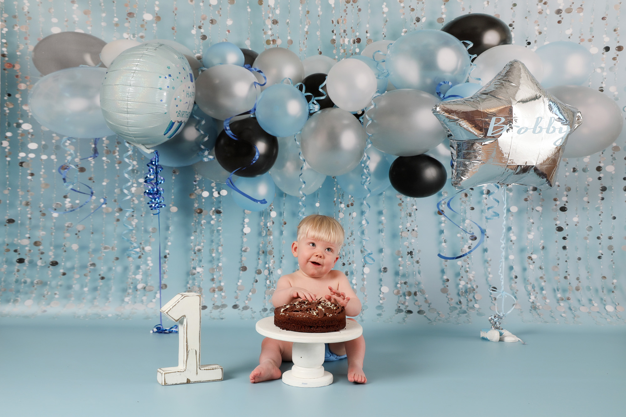 first birthday cakesmash baby boy smiling with blue balloon backdrop