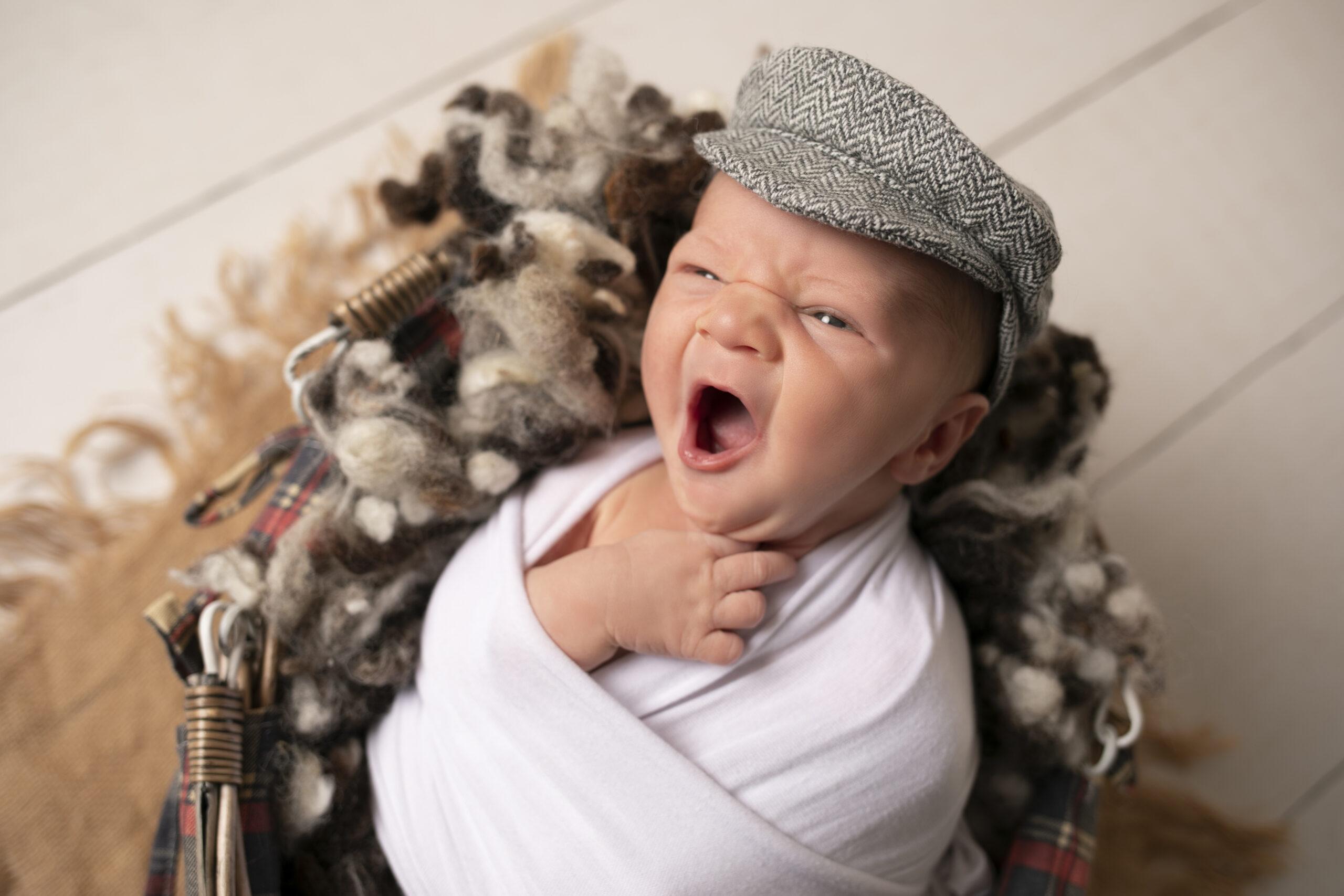 Peekaboo Liverpool newborn baby yawning wearing a flat cap