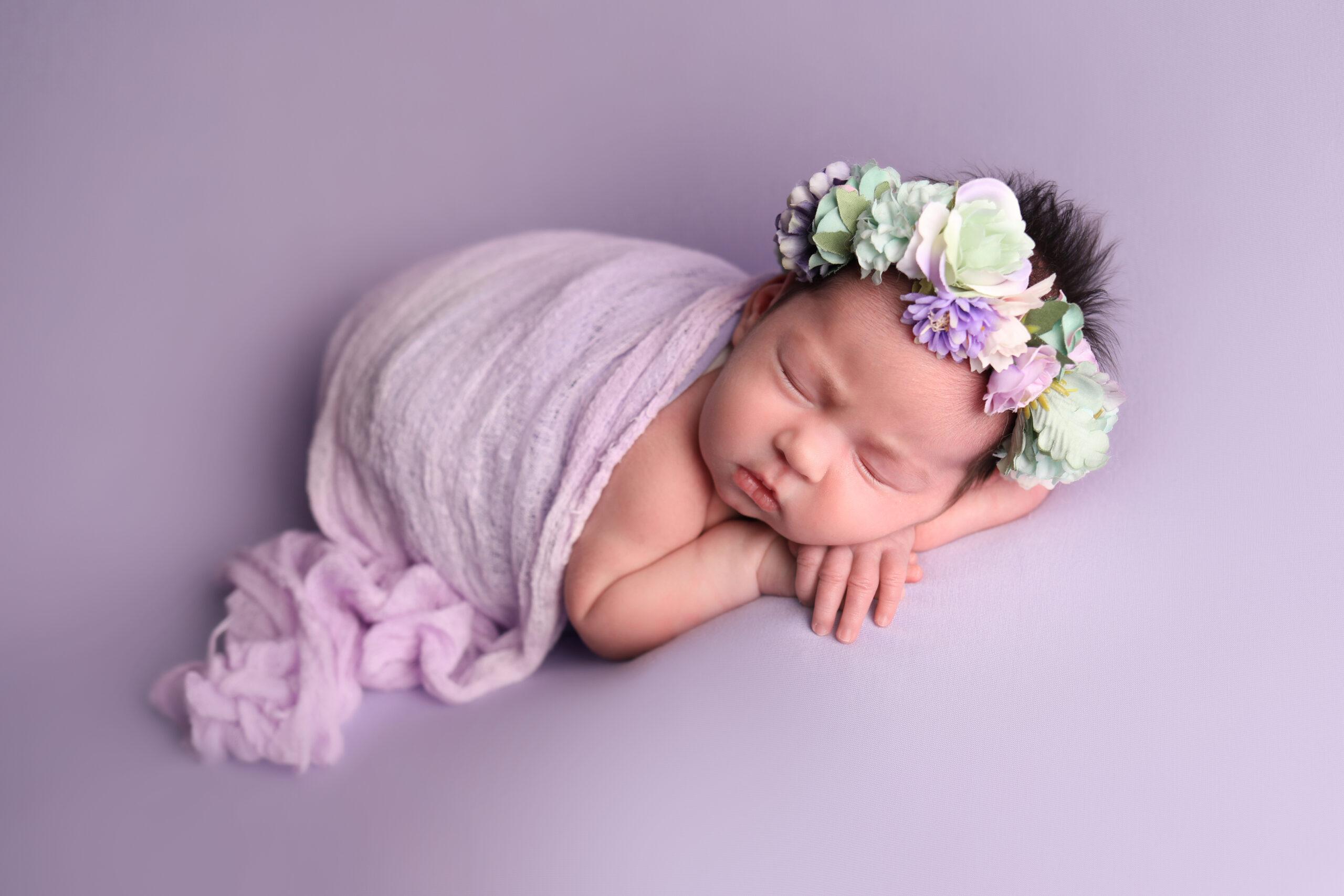 newborn baby girl portrait in deep pink rap holding small pink heart