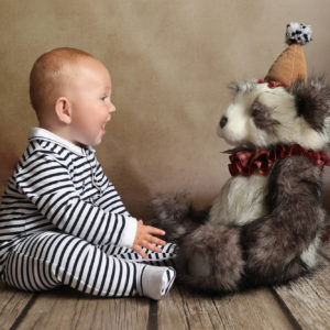 baby photoshoot little boy toddler in striped onesie smiling at teddy bear