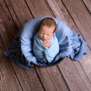 Baby boy wearing blue swaddle in tin bucket photo