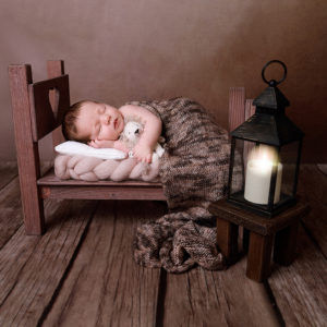 Baby boy in tiny bed photoshoot