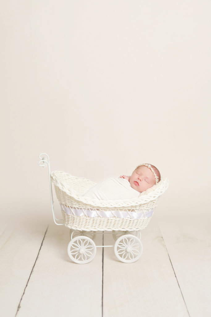 newborn baby girl in tiny vintage pram