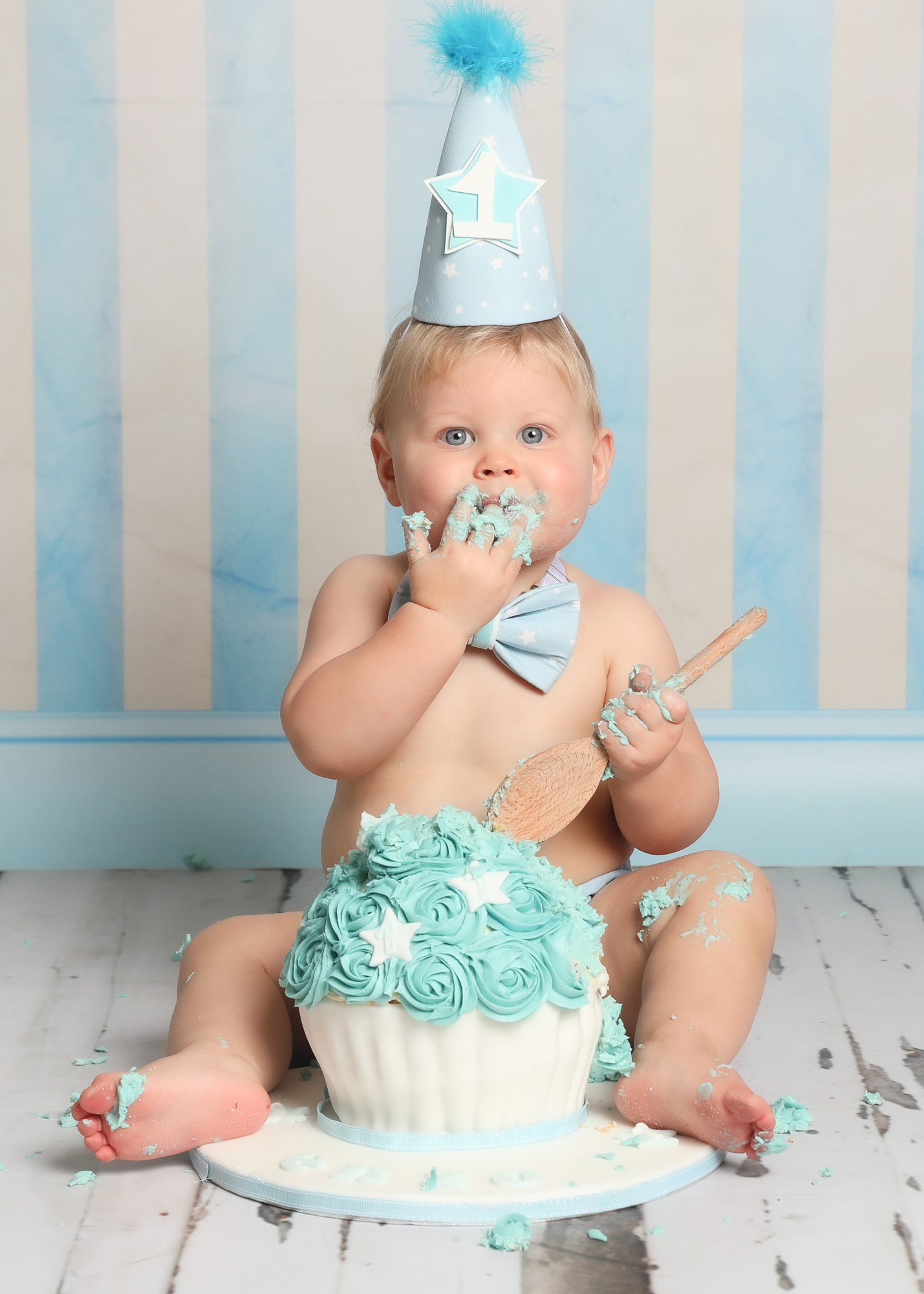 first birthday cakesmash baby boy smiling in party hat with blue stripe backdrop