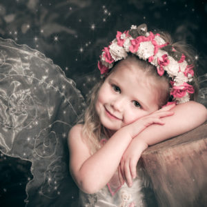little girl dressed as fairy with wings and flower headband in enchanted woodland photoshoot