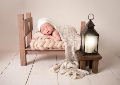newborn baby portrait in tiny brown bed sleeping