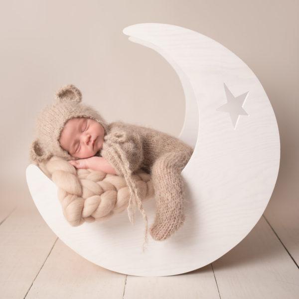 newborn photoshoot baby dressed as teddy bear sleeping in moon prop