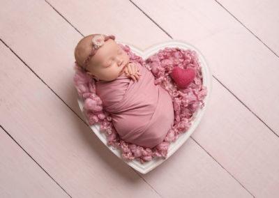 newborn baby girl photoshoot pink headband sleeping in pink heart shaped bowl