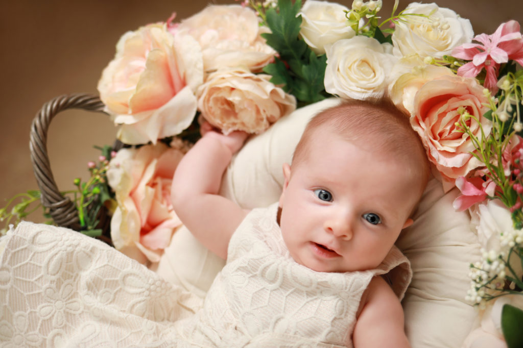 newborn baby girl with flowers for photoshoot