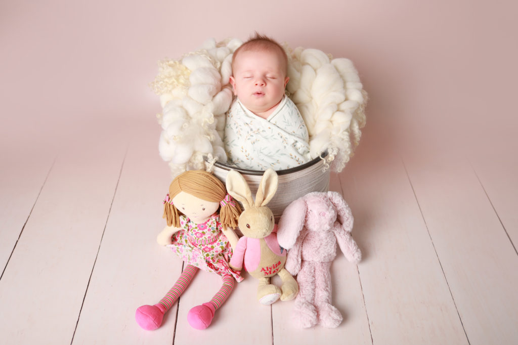 Baby in a bucket with teddies for photoshoot