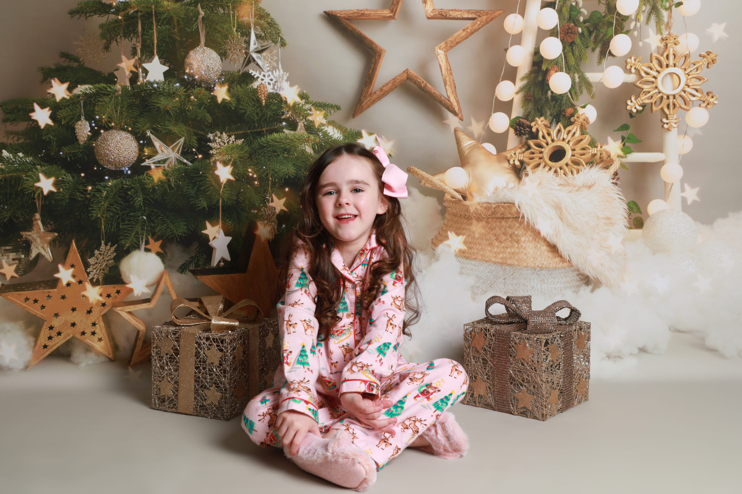 little girl sitting by gold decorated christmas tree with gifts