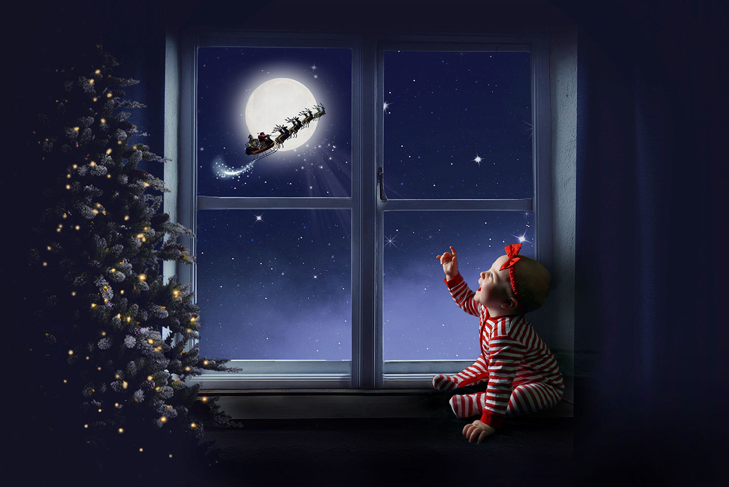 baby girl sitting by christmas tree looking out of window at Santa's sleigh flying by